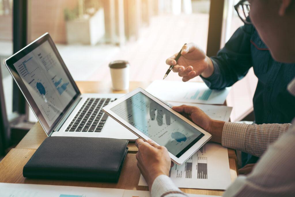 Compañeros de trabajo de la asociación empresarial que utilizan una tableta para trazar el informe de los estados financieros de la empresa y las ganancias, el progreso del trabajo y la planificación en la sala de la oficina