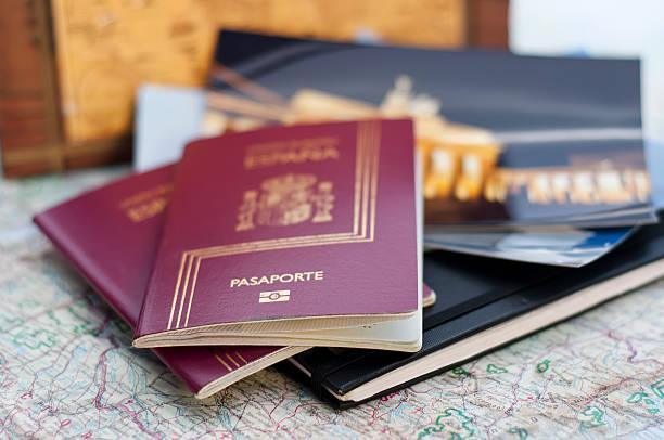 Pasaportes españoles encima de libretas, fotos de viajes y un mapa