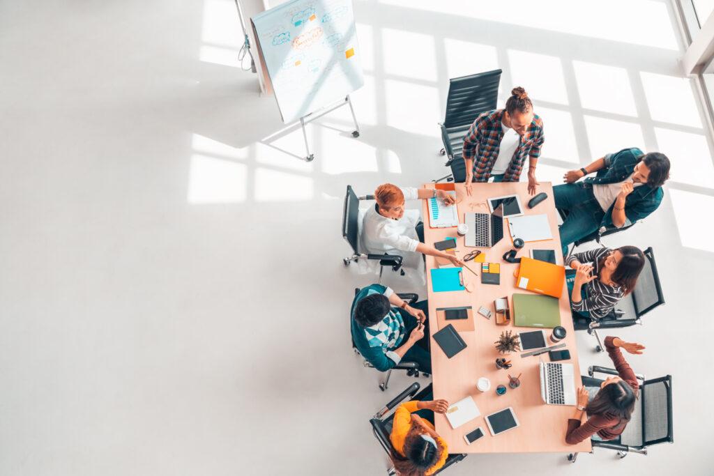 Grupo diverso multiétnico de compañeros de trabajo de negocios en la discusión de la reunión del equipo, oficina moderna de vista superior con espacio de copia.